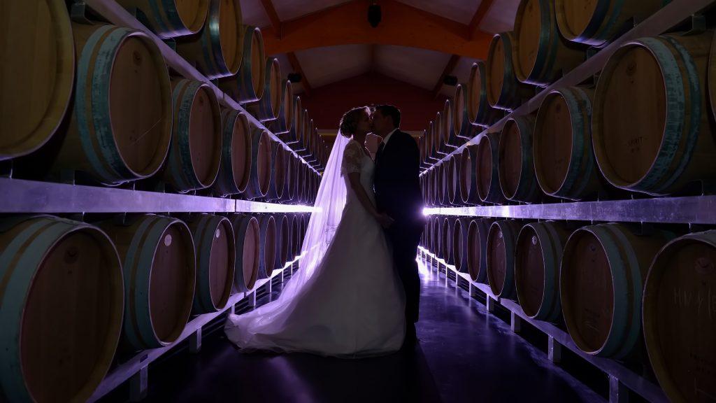 Mariés en contre jour au milieu des tonneaux du chai UNI MEDOC